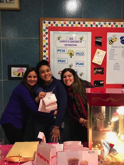 Three teachers holding bags of popcorn