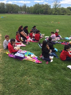 Students and teachers sitting on the lawn