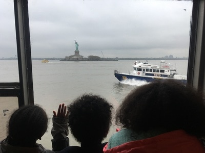 Students looking out a window toward the Statue of Liberty