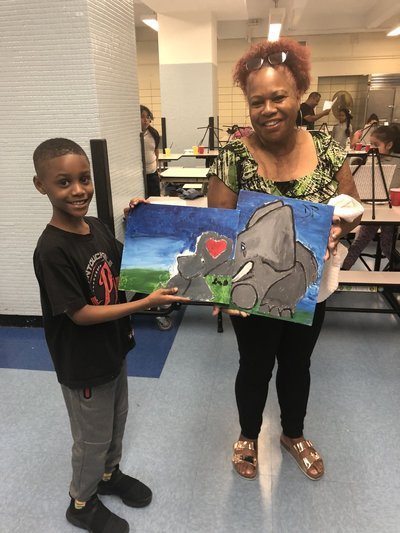 Woman and child with their paints of two elephants embracing tusks
