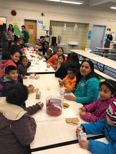 Parents and students sitting together at cafeteria tables