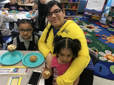 Mom and two students holding their muffins
