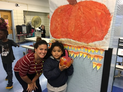 Teacher and student in front of a pumpkin painting