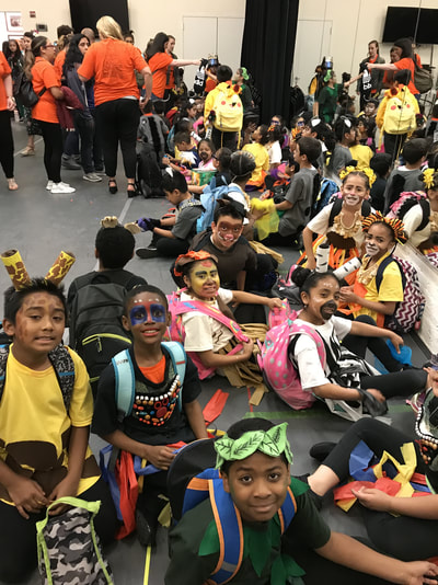 Students in costume and face paint sitting together