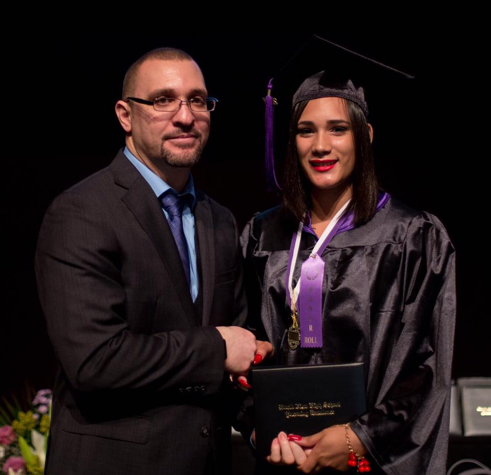 Principal posing for picture with graduate