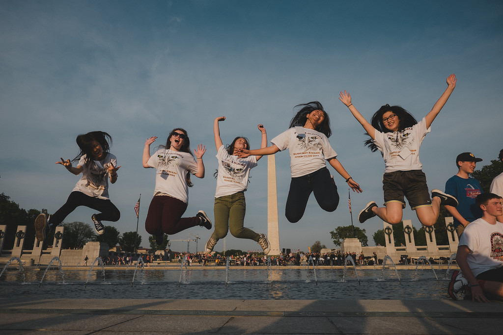 Students jumping in front of the Washington Monument