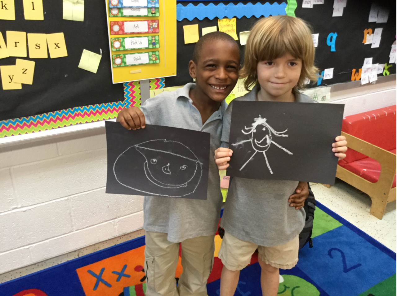 Two students and their drawings of smiling figures