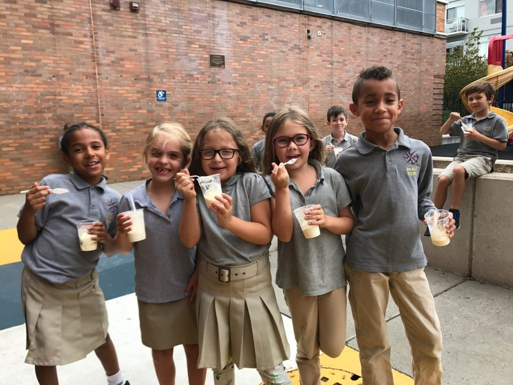 Five students eating pudding from cups