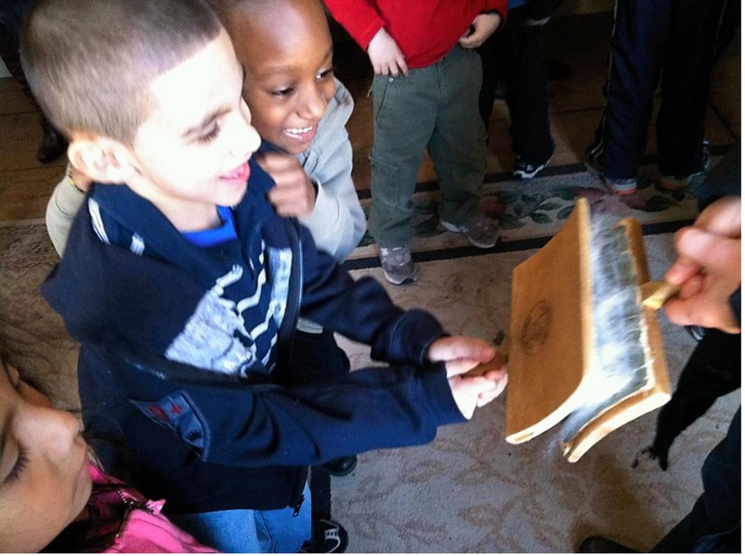 Kindergarteners brushing wool during a Fabric Study field trip