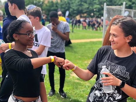Two students fist-bumping