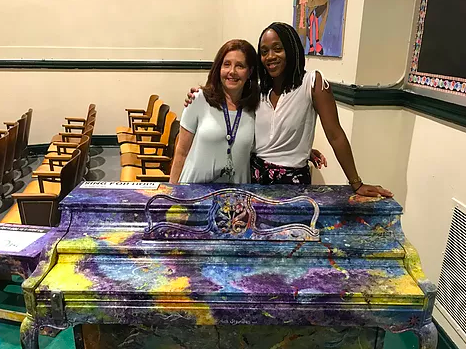 Principal Agard and Art Teacher Ms. Goldfarb pose with our new piano