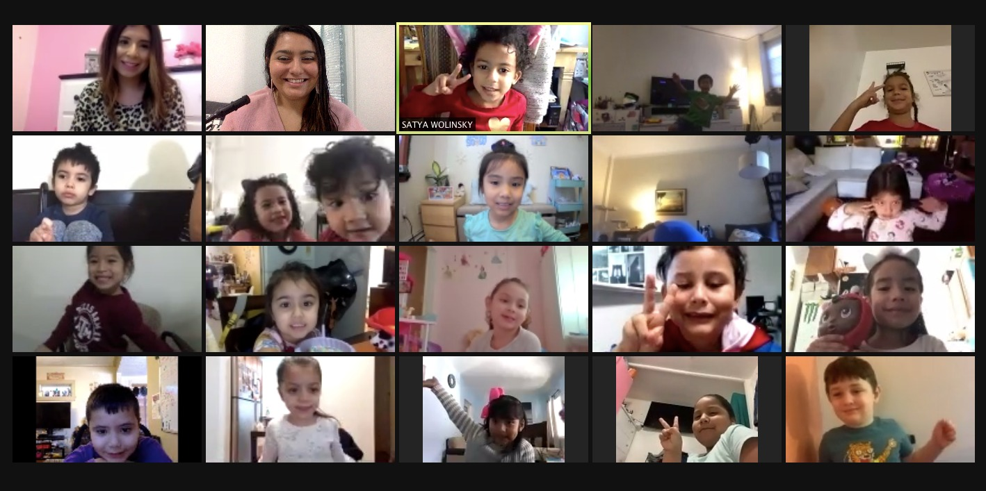 Students hold up peace signs to their teachers and classmates on a Zoom call