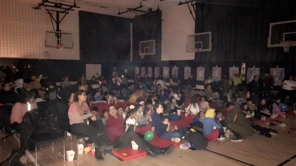 Families in the school gymnasium for movie night