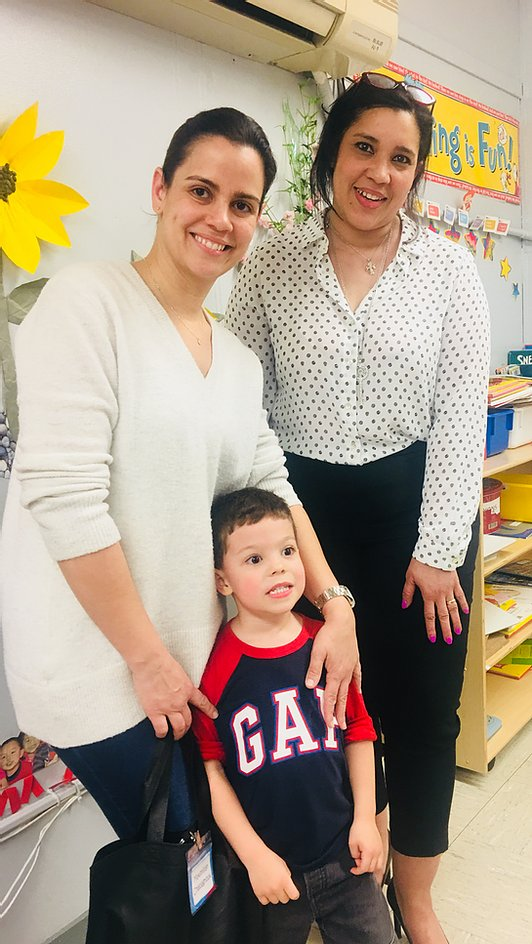 Principal Erica Ureña-Thus with a student and his parent standing in the classroom