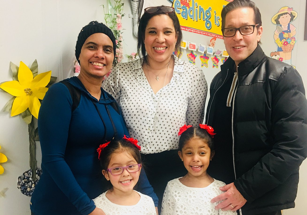 Principal Erica Ureña-Thus with two students wearing matching hair bows and their parents