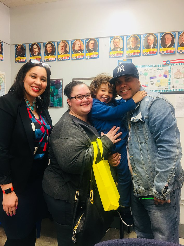 Principal Erica Ureña-Thus with a student with his arms around his parents