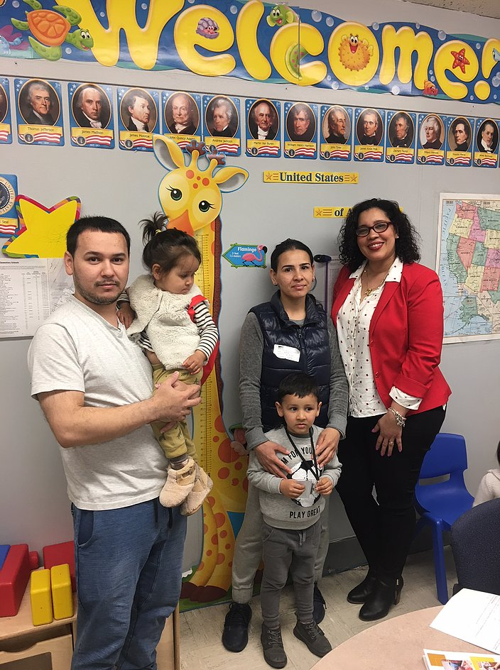Principal Erica Ureña-Thus with two students and their parents in front of a classroom wall