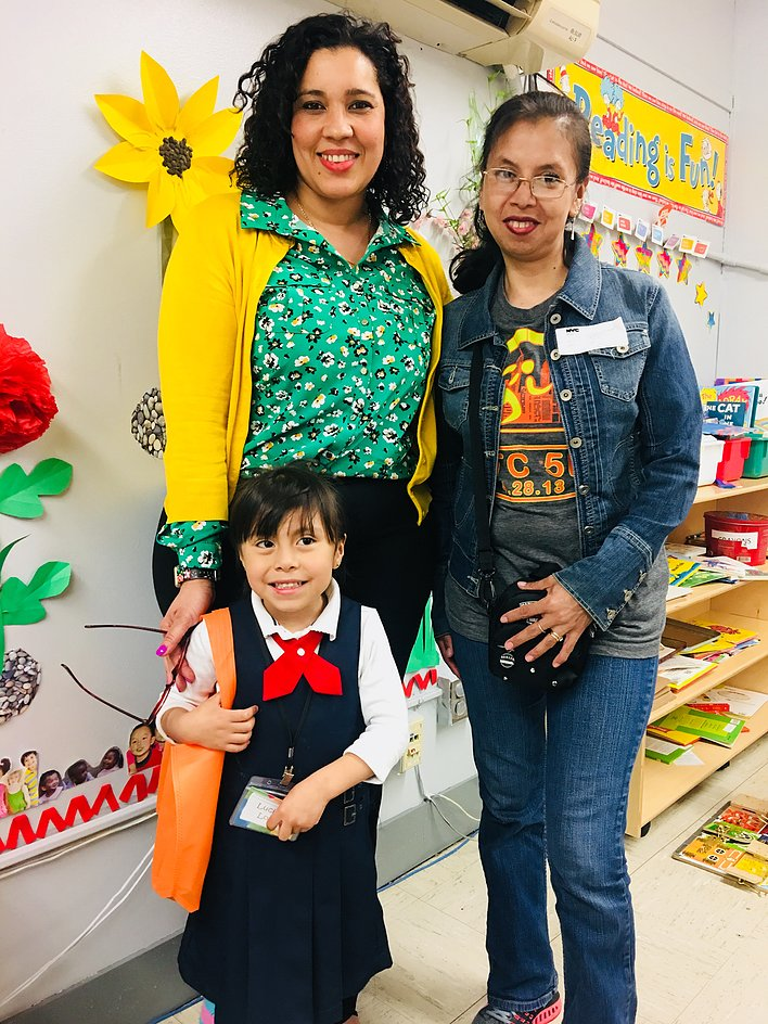 Principal Erica Ureña-Thus with her hand on a student in pink, standing with her parent