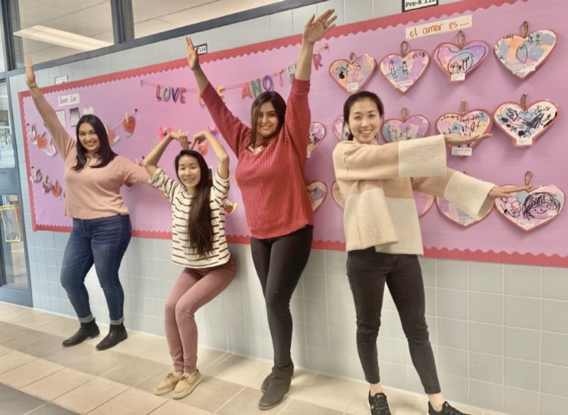 Teachers spelling out the word love with their arms and body