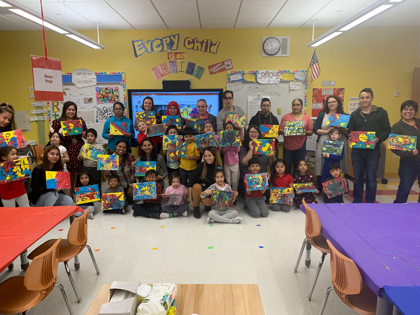 Families sharing their artwork during paint night
