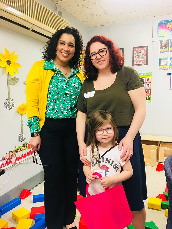 Principal Erica Ureña-Thus with a student wearing classes, standing with her parent