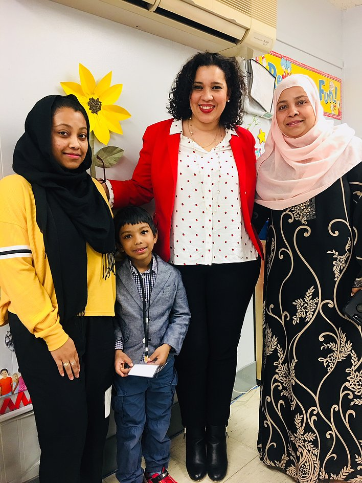 Principal Erica Ureña-Thus with two women wearing hijabs and a student