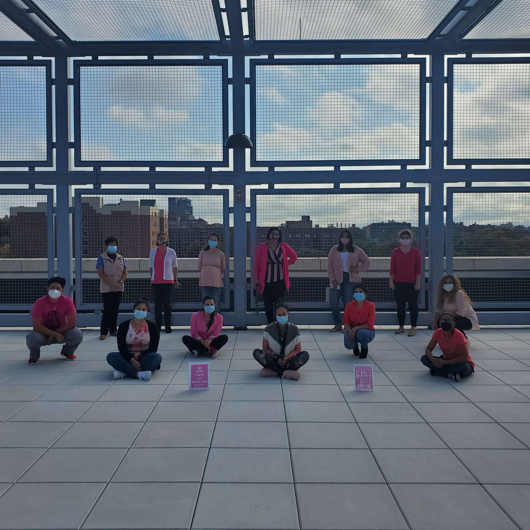 Teachers gathered on the rooftop dressed in pink for breast cancer awareness