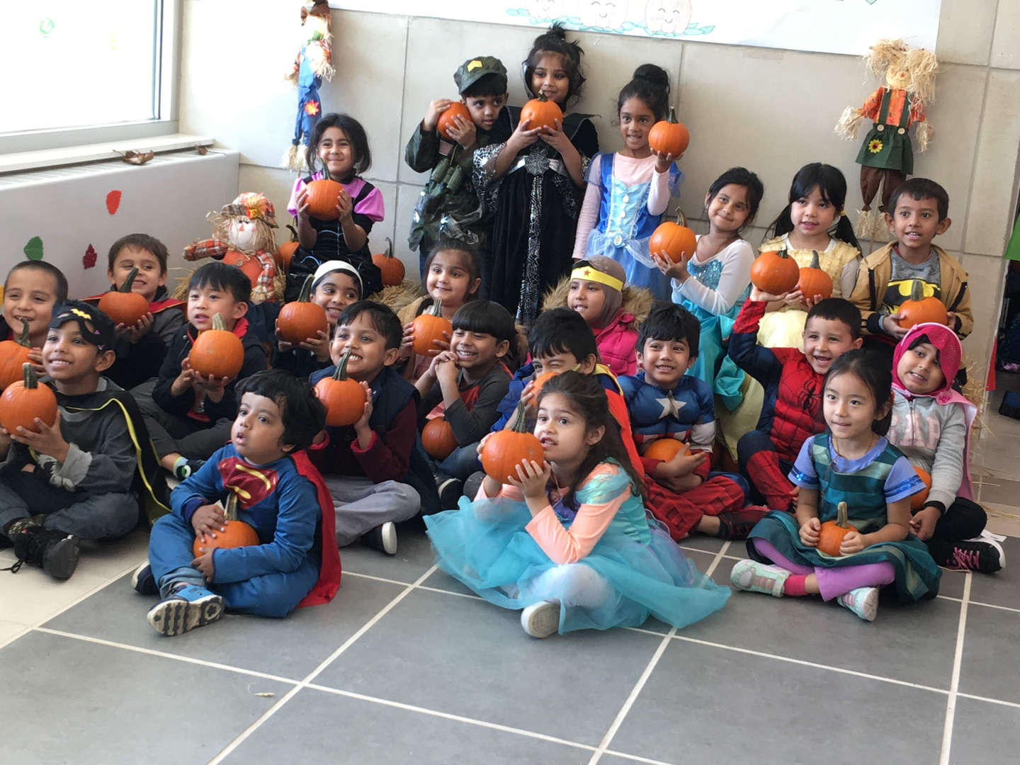 Teachers and students dressed up for halloween with pumpkins