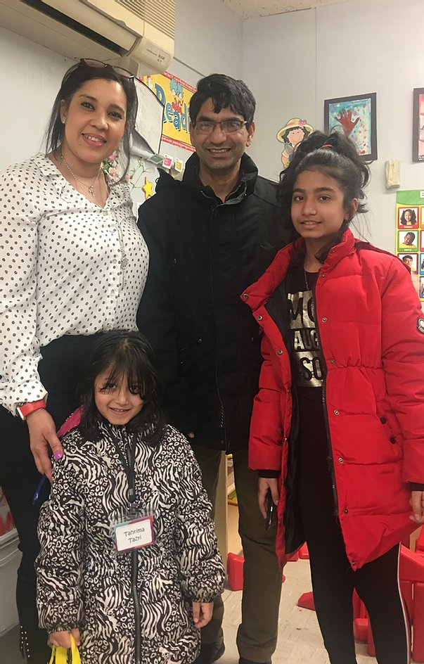 Principal Erica Ureña-Thus with two students and their parent in winter coats