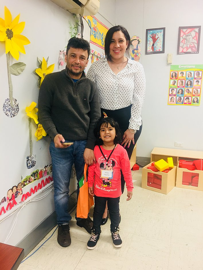Principal Erica Ureña-Thus with a student in pink and her parent standing in a classroom