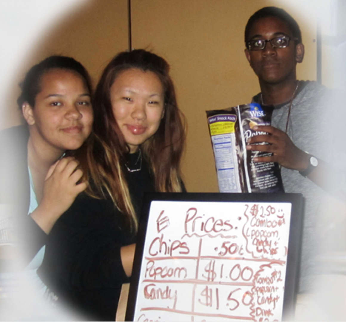 Students standing next to a white board menu
