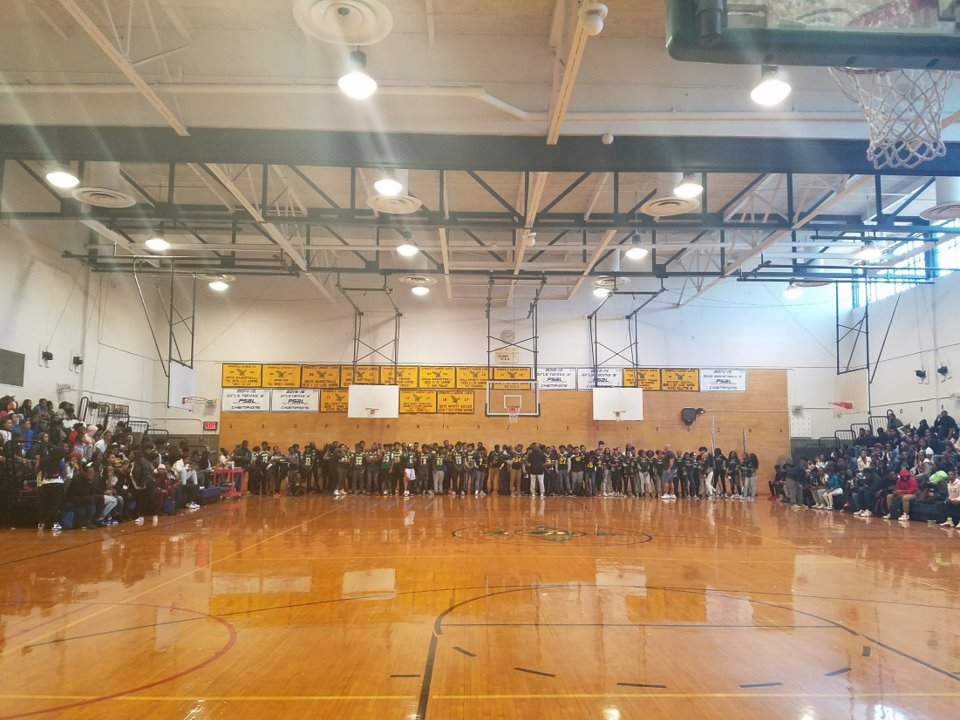 Students gathered in the gymnasium, some standing or sitting on the bleachers