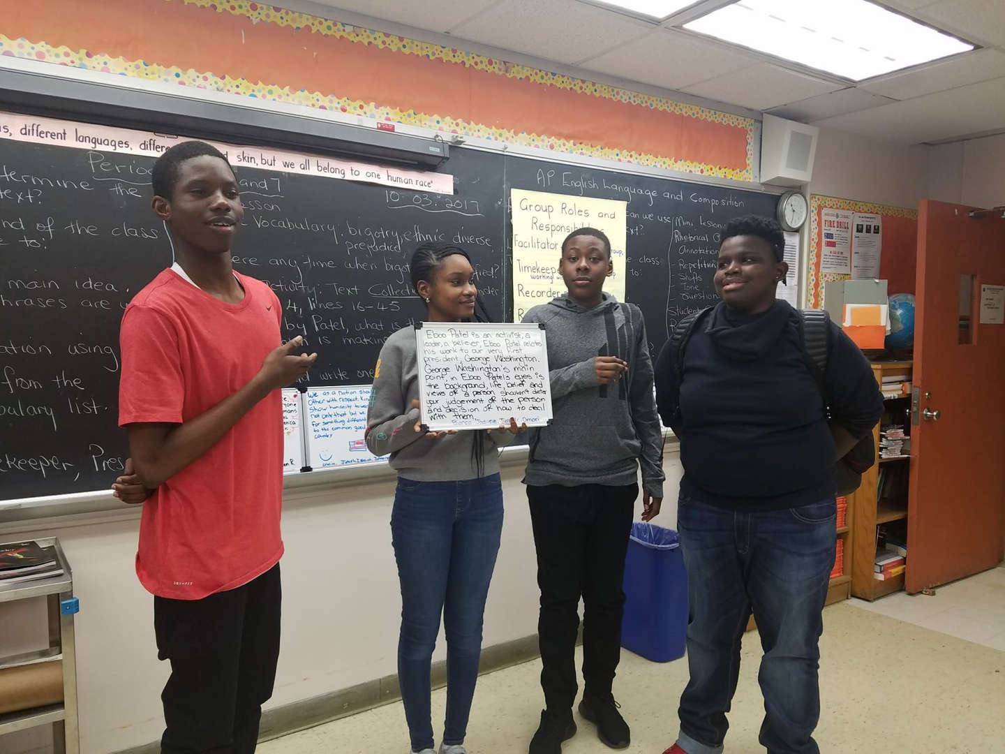 Four students presenting off a white board in class