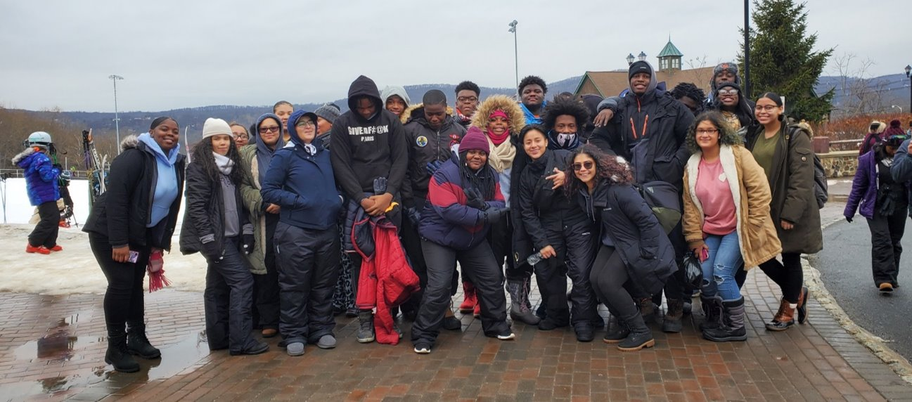 Students in winter coats huddled together outdoors