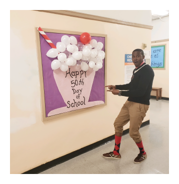 Principal Baptiste next to a 50th Day of School sign