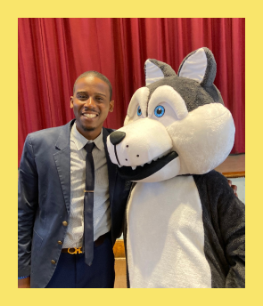 Principal Baptiste standing next to the school mascot