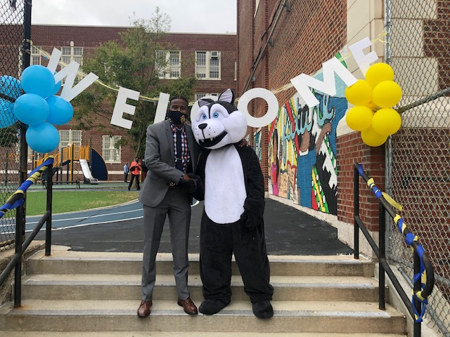 Principal Baptiste and school mascot shaking hands in front of the school and a welcome sign