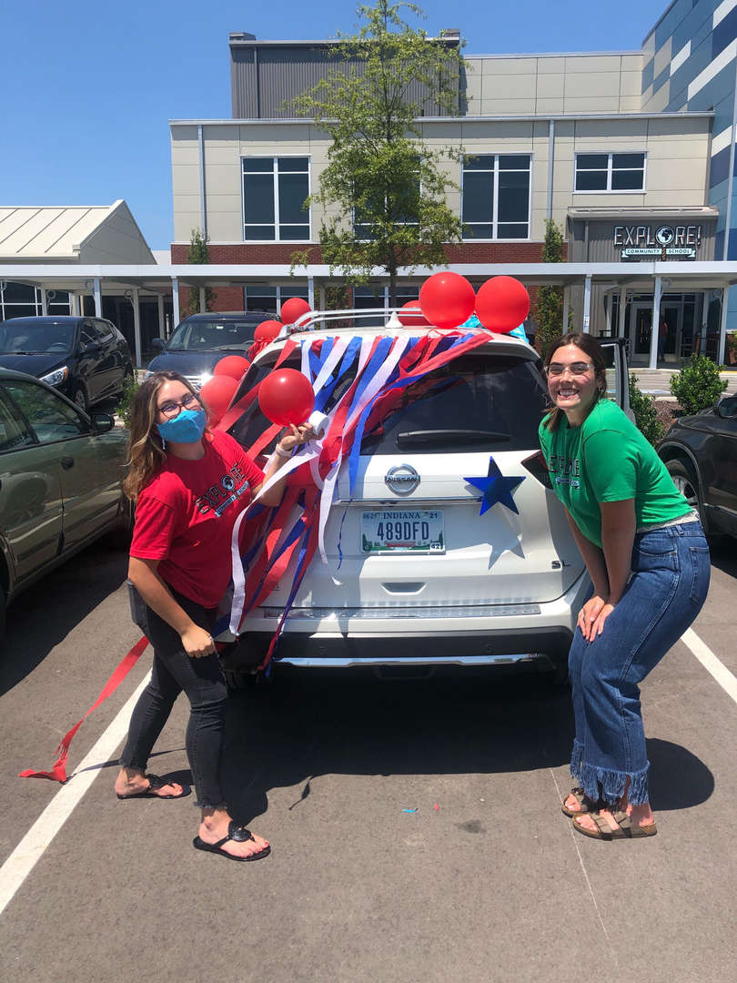 Two teachers showing their decorated car