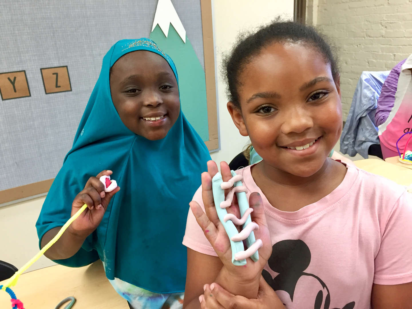 Two students holding up their clay crafts