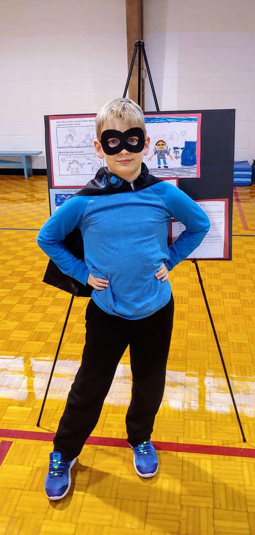 Student showcasing work in superhero costume
