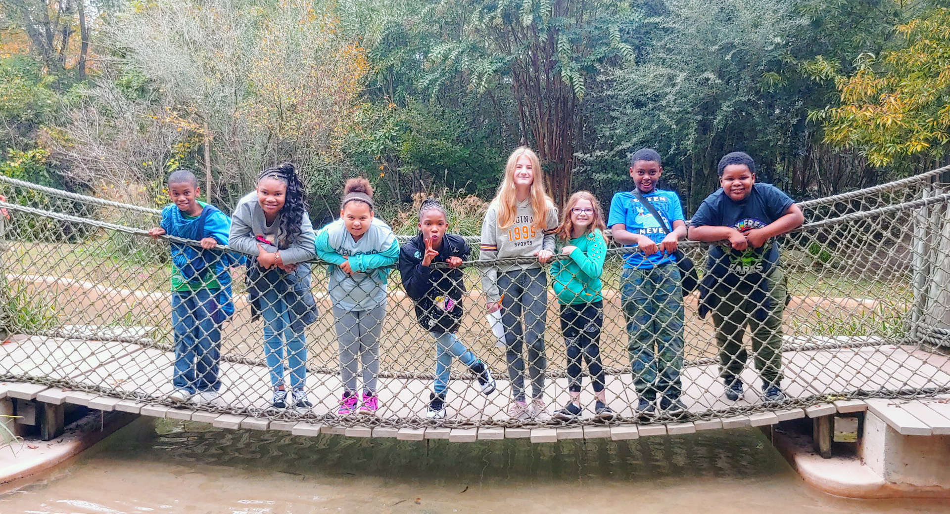 Eight students standing outdoors on a bridge