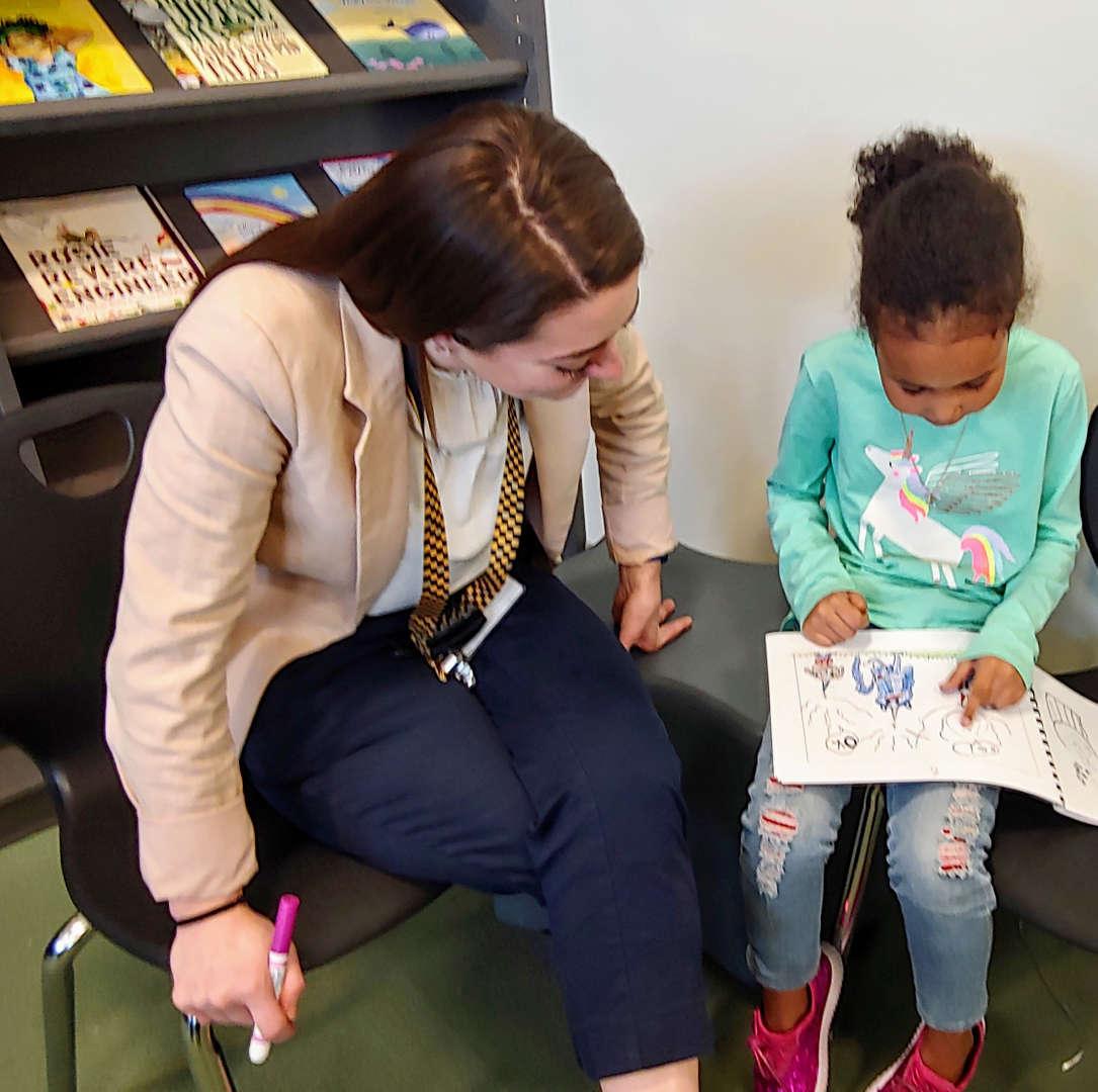 Student reading their book to teacher