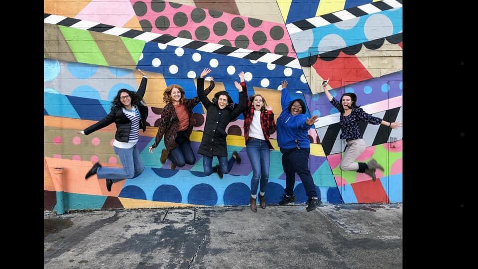 Staff jumping in front of mural
