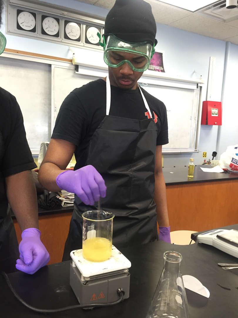 Student stirs a substance with gloved hands