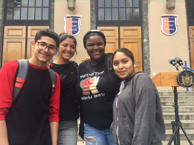 Four students standing at the steps of a building