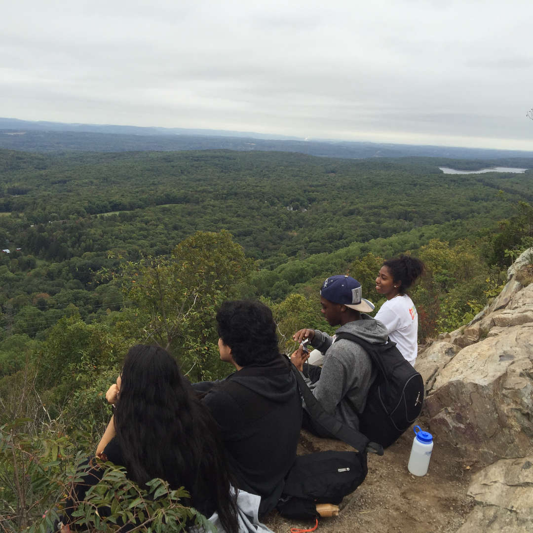 Four students enjoy their food as they sit on the side of a cliff overlooking a field of trees