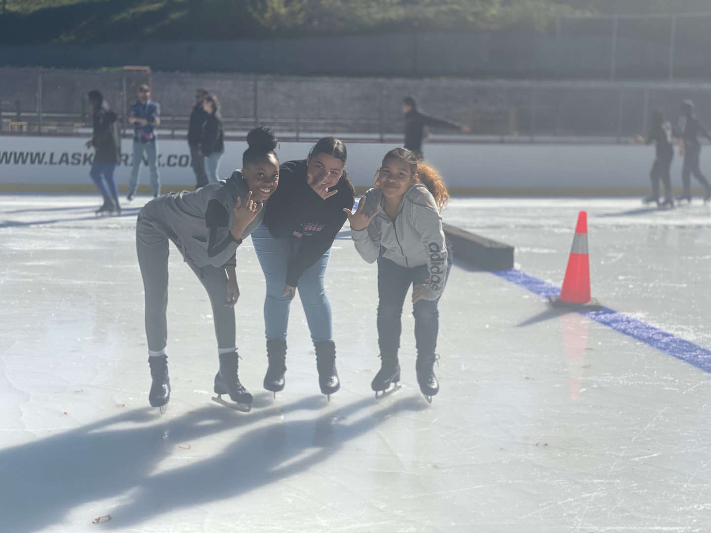 Three students pose on the ice skating rink