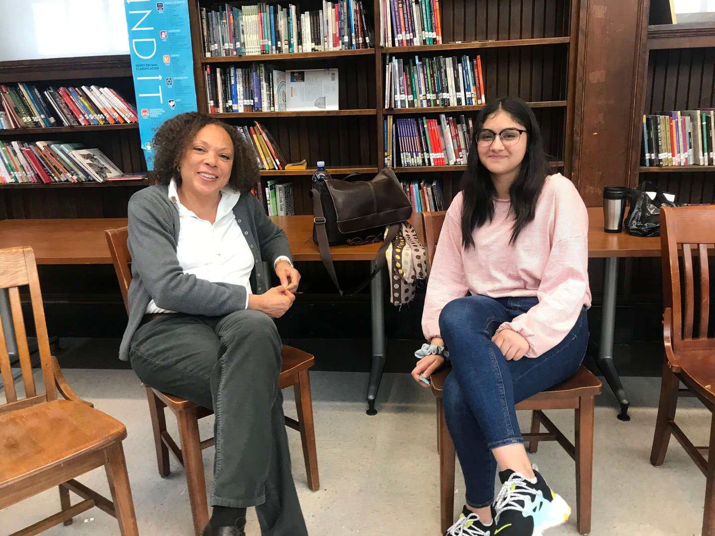 Student sitting with a member of the administration in the library
