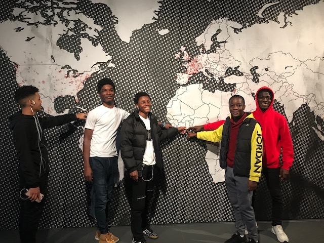 Students in front of a wall map with their hand on Africa