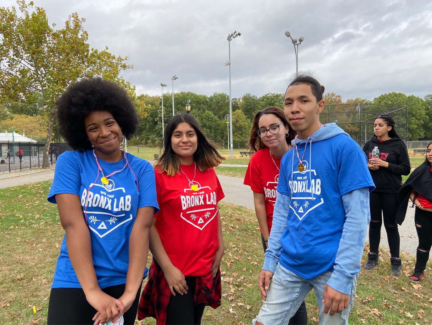 Students wearing colorful Bronx Lab t-shirts stand on the lawn